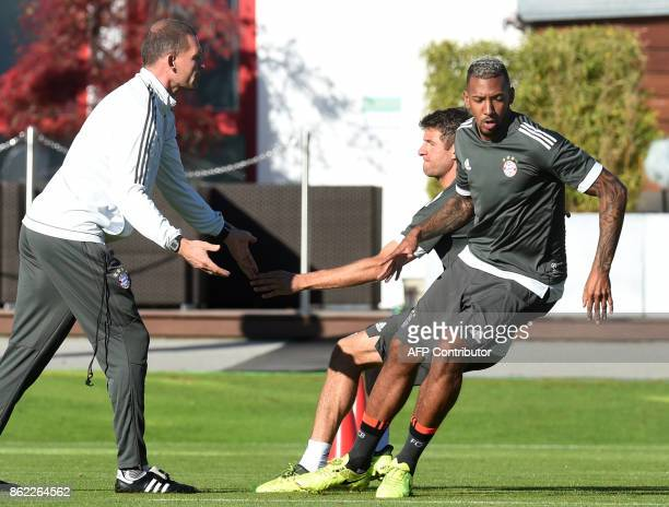 Bayern Munich's defender Jerome Boateng and Bayern Munich's striker Thomas Mueller train with fitness trainer Holger Broich during a training session...