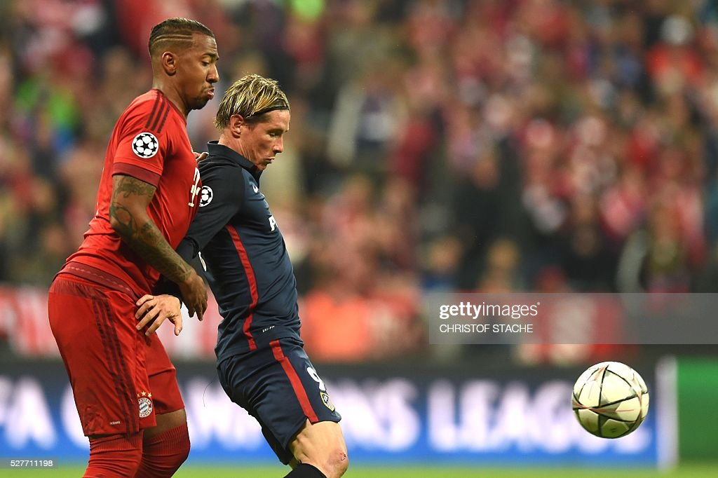 Bayern Munich's defender Jerome Boateng (L) and with Atletico Madrid's forward Fernando Torres fight for the ball during the UEFA Champions League semi-final, second-leg football match between FC Bayern Munich and Atletico Madrid in Munich, southern Germany, on May 3, 2016. / AFP / Christof Stache