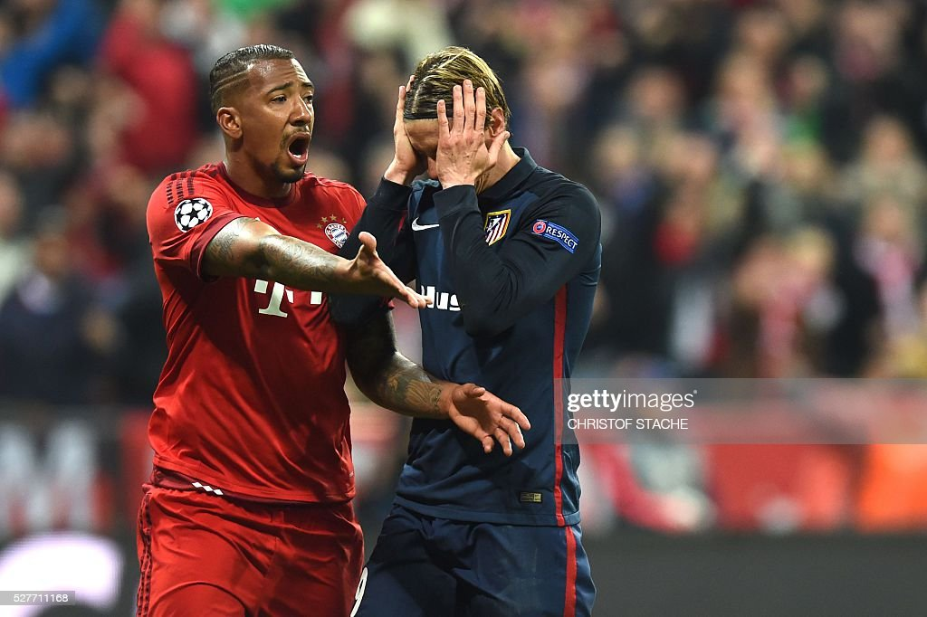 Bayern Munich's defender Jerome Boateng (L) argues with Atletico Madrid's forward Fernando Torres during the UEFA Champions League semi-final, second-leg football match between FC Bayern Munich and Atletico Madrid in Munich, southern Germany, on May 3, 2016. / AFP / Christof Stache