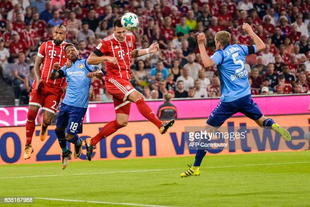 Bayern Munich's defender Niklas Suele heads the ball to score the opening goal of the season during the German First division Bundesliga football...
