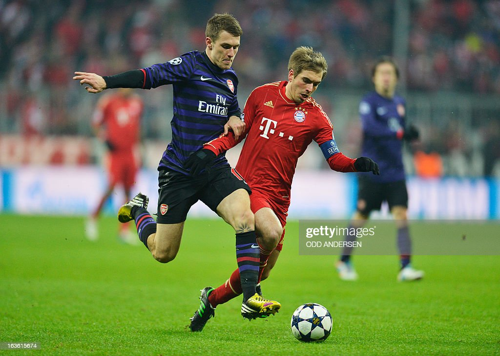 Bayern Munich's defender Philipp Lahm and Arsenal´s Welsh midfielder Aaron Ramsey (L) vie for the ball during the UEFA Champions League Round of 16 second-leg football match FC Bayern Munich vs FC Arsenal London at the Allianz arena in Munich, southern Germany, on March 13, 2013.