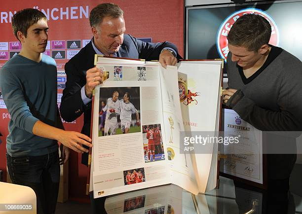 Bayern Munich's defender Philipp Lahm Bayern Munich's President KarlHeinz Rummenigge and midfielder Bastian Schweinsteiger leaf through a new Bayern...