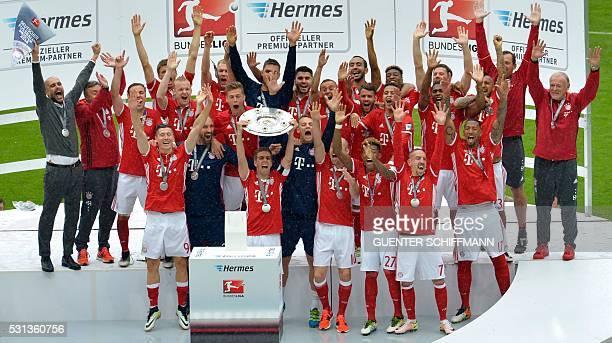 Bayern Munich's defender Philipp Lahm holds the Bundesliga trophy aloft celebrating with tem mates after the German first division Bundesliga...