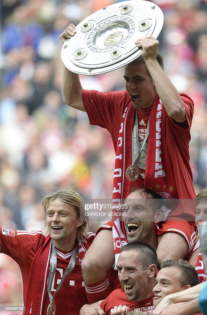 Bayern Munich's defender Philipp Lahm (C) holds the German football league champion's trophy as he celebrates with teammates after winning 3:0 the German first division Bundesliga football match Bayern Munich vs FC Augsburg in Munich, southern Germany, on May 11, 2013. Munich were confirmed German league champions back on April 6, when they won the Bundesliga with a record six games left to play.