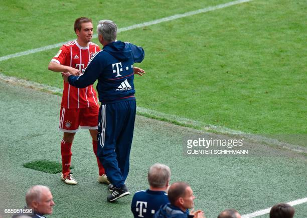 Bayern Munich's defender Philipp Lahm is embraced by Bayern Munich's Italian head coach Carlo Ancelotti as he leaves the pitch during the German...
