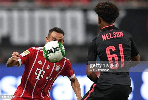 Bayern Munich's defender Rafinha and Arsenal Reiss Nelson vie for the ball during the International Champions Cup football match between Bayern...