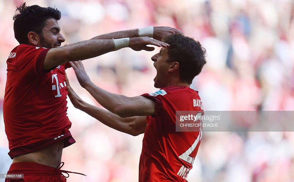 Bayern Munich's defender Serdar Tasci (L) and Bayern Munich's striker Thomas Mueller celebrate after the first goal during the German first division Bundesliga football match Bayern Munich vs Borussia Moenchengladbach in Munich, southern Germany, on April 30, 2016. / AFP / CHRISTOF