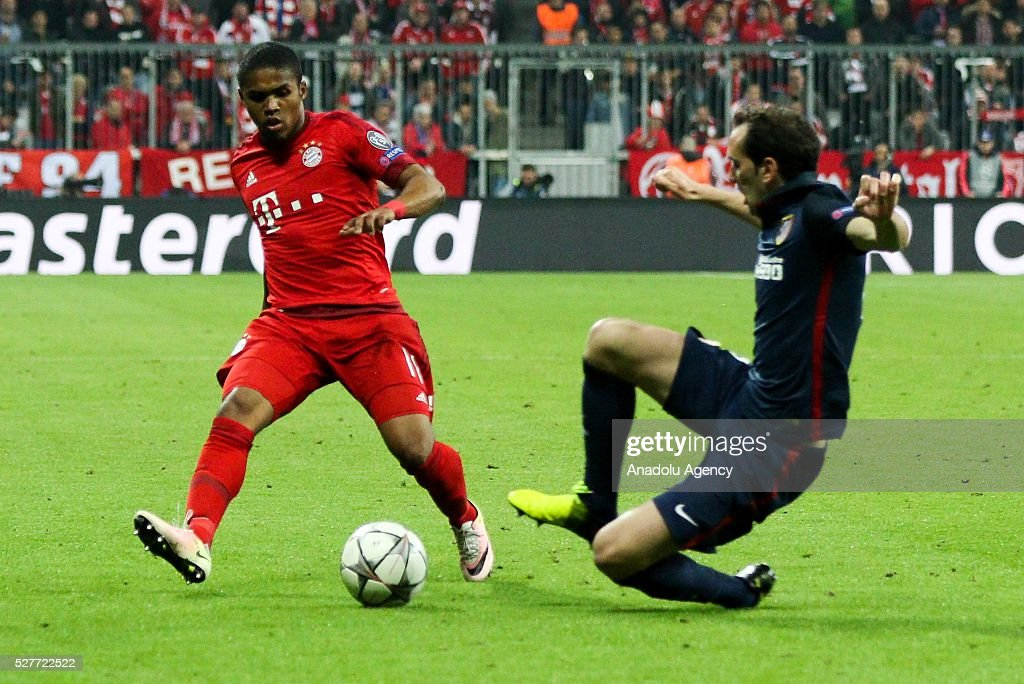 Bayern Munich's Douglas Costal (L) and Diego Godin of Atletico Madrid (R) vie for the ball during the UEFA Champions League semifinal second leg soccer match between FC Bayern Munich and Atletico Madrid at the Allianz Arena in Munich, Germany on May 3, 2016.