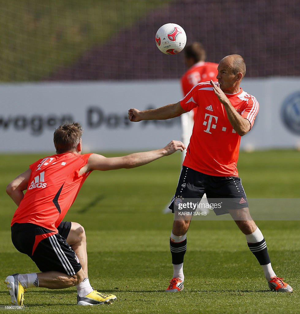 Bayern Munich's Dutch midfielder Arjen Robben (R) and German midfielder Bastian Schweinsteiger (L) attend a training session at the Aspire Academy for Sports Excellence in Doha on January 6, 2013. Bayern Munich is in Qatar for a week-long training camp before the beginning of the new season of the German Bundesliga after the winter break. AFP PHOTO/KARIM SAHIB