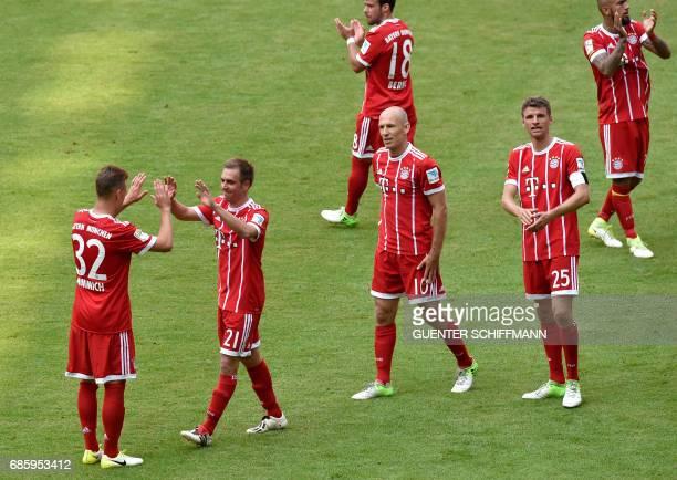 Bayern Munich's Dutch midfielder Arjen Robben Bayern Munich's forward Thomas Mueller look at Bayern Munich's defender Philipp Lahm clapping hands...