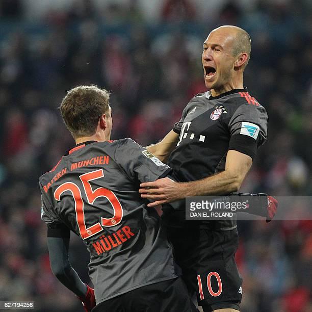Bayern Munich's Dutch midfielder Arjen Robben celebrates scoring the 21 goal with Bayern Munich's forward Thomas Mueller during the German first...