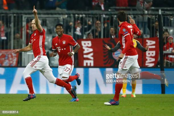 Bayern Munich's Dutch midfielder Arjen Robben celebrates scoring the opening goal with his teammates during the UEFA Champions League round of...