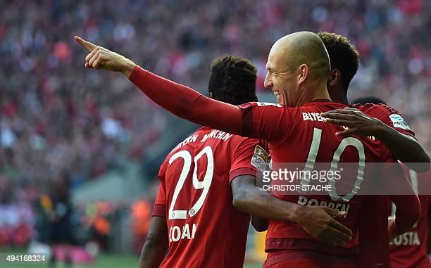 Bayern Munich's Dutch midfielder Arjen Robben celebrates with teammates after scoring during the German first division football Bundesliga match...