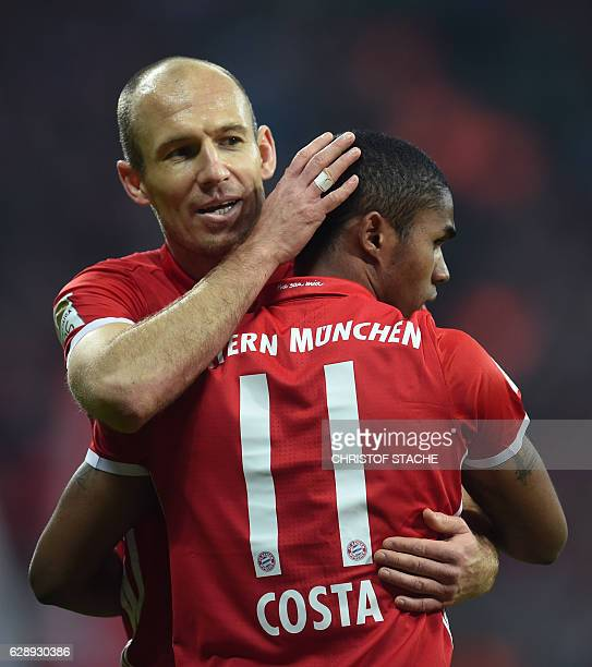 Bayern Munich's Dutch midfielder Arjen Robben embraces Bayern Munich's Brazilian midfielder Douglas Costa after the fifth goal during the German...