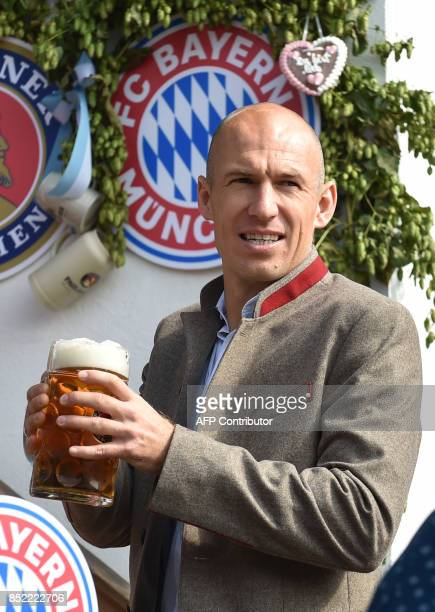 Bayern Munich's Dutch midfielder Arjen Robben holds a beer mug as he poses during the traditional visit of members of German first division...