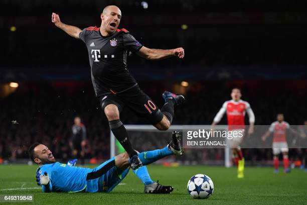 TOPSHOT Bayern Munich's Dutch midfielder Arjen Robben is tackled by Arsenal's Colombian goalkeeper David Ospina during the UEFA Champions League last...