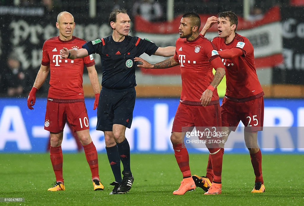 Bayern Munich's Dutch midfielder Arjen Robben (L), Referee Florian Meyer (2nd L), Bayern Munich's striker Thomas Mueller (R) walk with Bayern Munich's Chilian midfielder Arturo Vidal (2ndR) after his injury from the field during the German first division Bundesliga football match of FC Augsburg vs FC Bayern Munich in Augsburg, southern Germany, on February 14, 2016. / AFP / CHRISTOF STACHE /