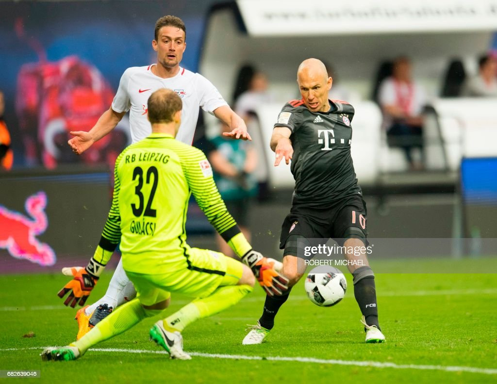 Bayern Munich's Dutch midfielder Arjen Robben (R) scores the 4-5 against Leipzig's Hungarian goalkeeper Peter Gulacsi during extra time of the German first division Bundesliga football match between RB Leipzig and FC Bayern Munich on May 13, 2017 in Leipzig, eastern Germany. /