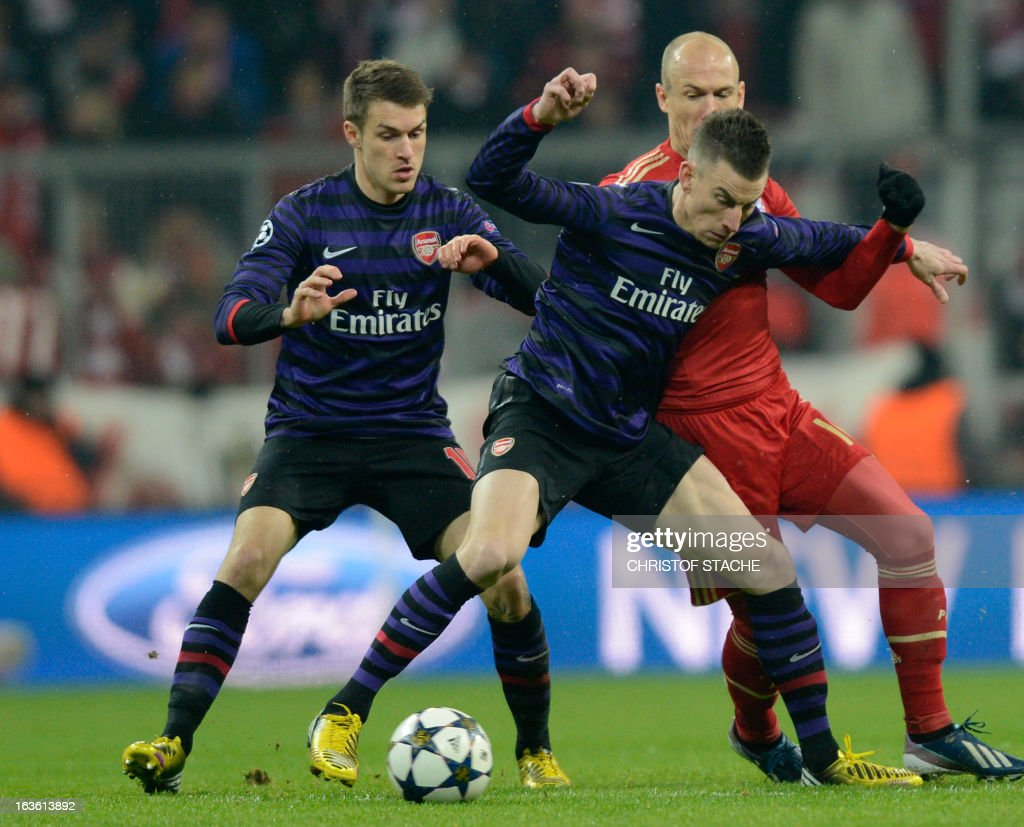 Bayern Munich's Dutch midfielder Arjen Robben (R) vies for the ball with Arsenal´s Welsh midfielder Aaron Ramsey and Arsenal´s Belgian defender Laurent Koscielny (C) during the UEFA Champions League Round of 16 second-leg football match FC Bayern Munich vs FC Arsenal London in Munich, southern Germany, on March 13, 2013.