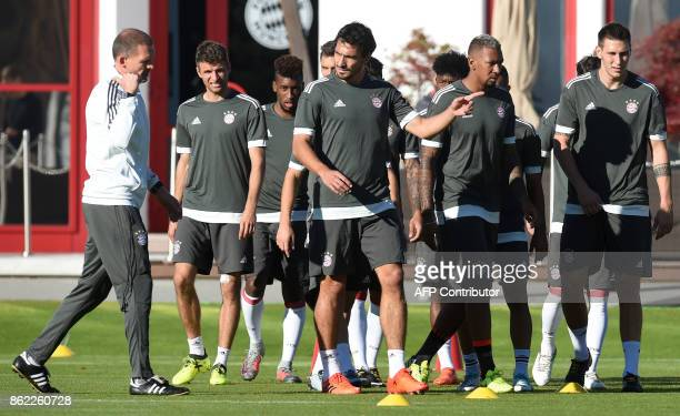 Bayern Munich's fitness trainer Holger Broich talks to players during a training session on the eve of the Champions League group B match between...
