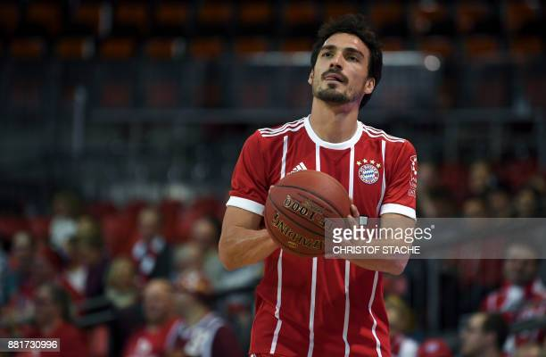 Bayern Munich's football defender Mats Hummels focuses to throw the ball during a basketball match at a sponsor fan event in Munich southern Germany...