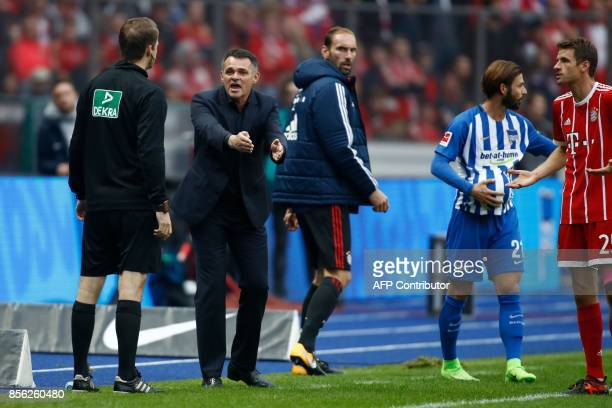 Bayern Munich's French interim head coach Willy Sagnol argues with the fourth offical during the German first division Bundesliga football match...