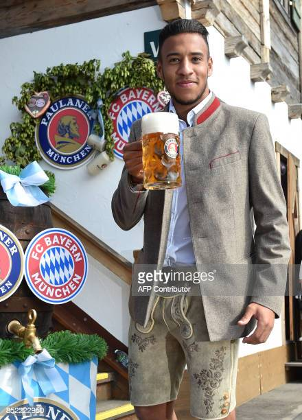 Bayern Munich's French midfielder Corentin Tolisso holds a beer mug as he poses during the traditional visit of members of German first division...