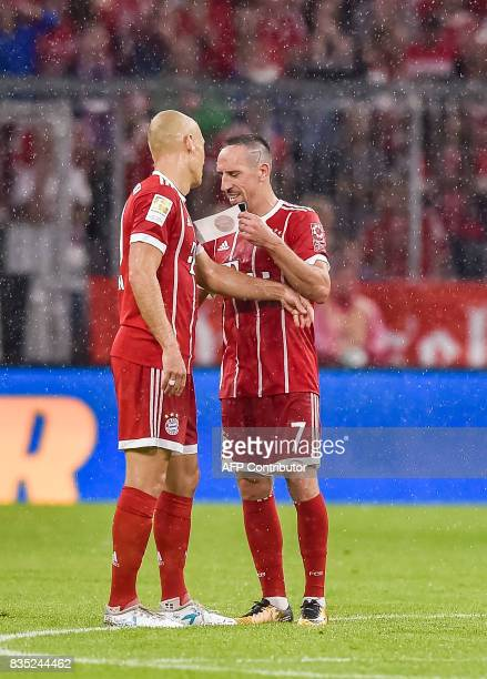 Bayern Munich's French midfielder Franck Ribery hands over the captains's armband to Bayern Munich's Dutch midfielder Arjen Robben during the German...