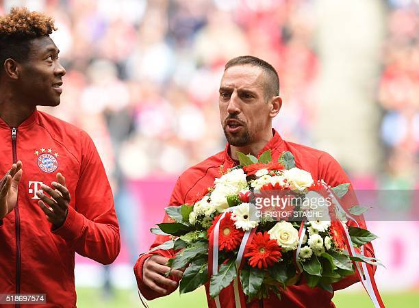 Bayern Munich's French midfielder Franck Ribery is applauded by Bayern Munich's Austrian midfielder David Alaba as he holds a bouquet of flowers he...