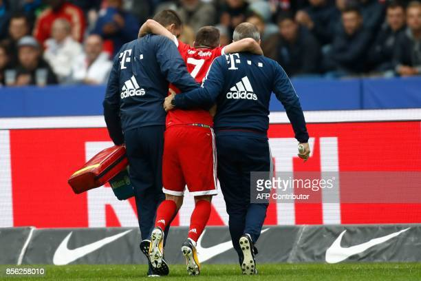 TOPSHOT Bayern Munich's French midfielder Franck Ribery is helped off the pitch by medical staff after injuring his knee during the German first...