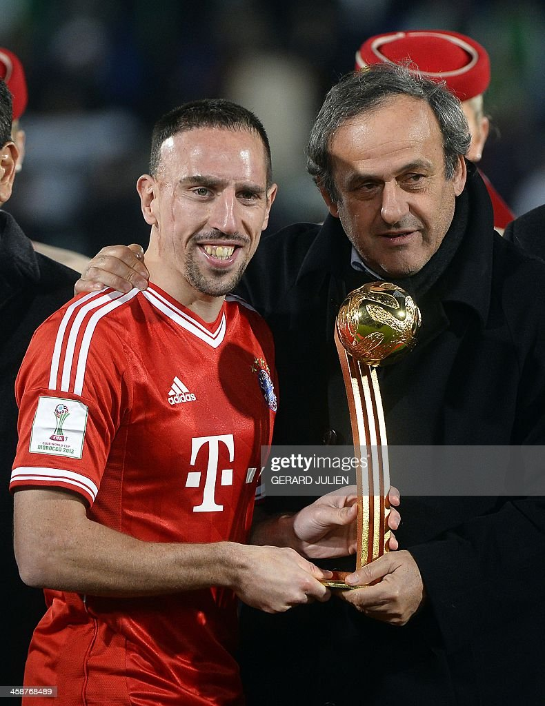 Bayern Munich's French midfielder Franck Ribery (L) poses with UEFA president <a gi-track='captionPersonalityLinkClicked' href=/galleries/search?phrase=Michel+Platini&family=editorial&specificpeople=206862 ng-click='$event.stopPropagation()'>Michel Platini</a> (R) and the player of the tournament trophy following the 2013 FIFA Club World Cup in the Moroccan city of Marrakesh, on December 21, 2013. Bayern defeated Raja 2-0 to win the cup. Ribery was named player of the tournament ahead of teammate Philipp Lahm and Raja's Iajour. AFP PHOTO / GERARD JULIEN