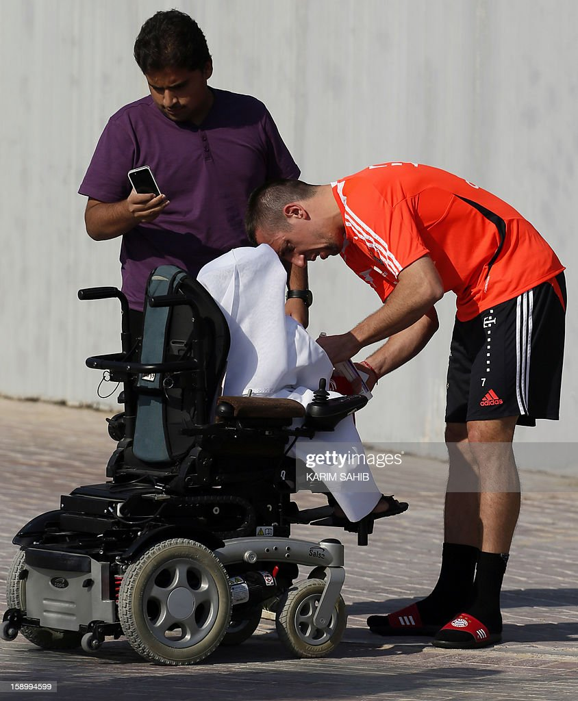 Bayern Munich's French midfielder Franck Ribery (R) signs an autograph for a fan during a training session at the Aspire Academy for Sports Excellence in Doha on January 5, 2013. Bayern Munich is in Qatar for a week-long training camp before the beginning of the new season of the German Bundesliga after the winter break. AFP PHOTO/KARIM SAHIB