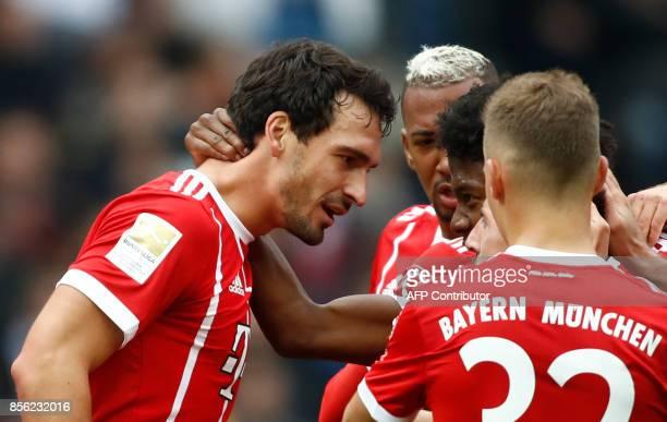 Bayern Munich's German defender Mats Hummels celebrates scoring the opening goal with his teammates during the German first division Bundesliga...