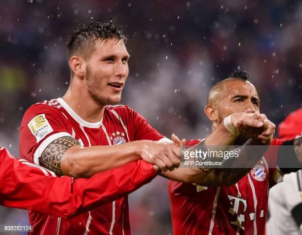Bayern Munich's German defender Niklas Suele celebrates victory next to Bayern Munich's Chilean midfielder Arturo Vidal after the German first...