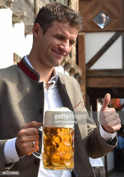 Bayern Munich's German forward Thomas Mueller holds a beer mug as he poses during the traditional visit of members of German first division...