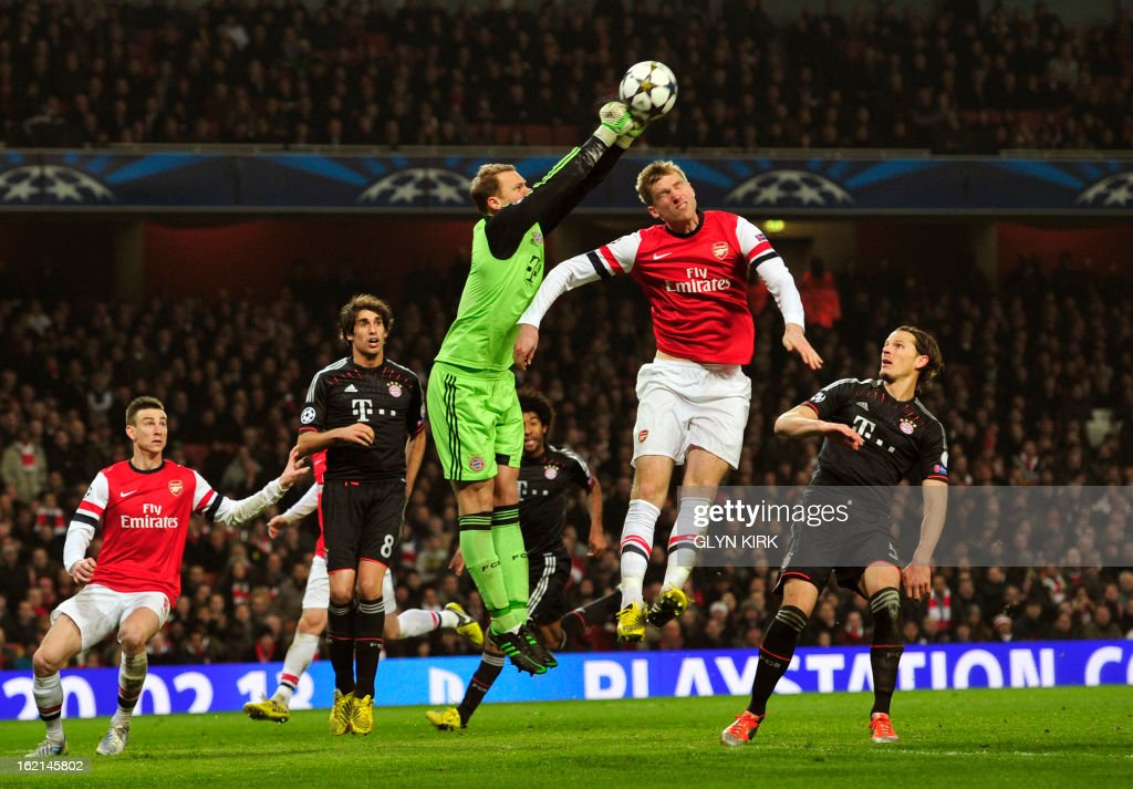 Bayern Munich's German goalkeeper Manuel Neuer (CL) punches the ball as Arsenal's German defender Per Mertesacker (CR) jumps to head during the UEFA Champions League round of 16 football match between Arsenal and Bayern Munich at the Emirates Stadium in north London on February 19, 2013. Bayern Munich won 3-1.