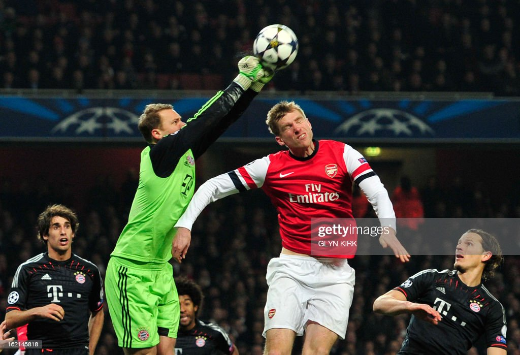 Bayern Munich's German goalkeeper Manuel Neuer (CL) punches the ball as Arsenal's German defender Per Mertesacker (CR) jumps to head during the UEFA Champions League round of 16 football match between Arsenal and Bayern Munich at the Emirates Stadium in north London on February 19, 2013. Bayern Munich won 3-1. AFP PHOTO / GLYN KIRK