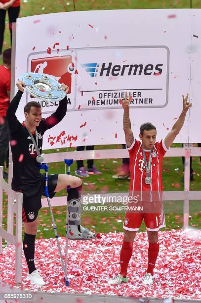 Bayern Munich's German keeper Manuel Neuer lifts the trophy next to Bayern Munich's Brazilian defender Rafinha during the celebrations after the...