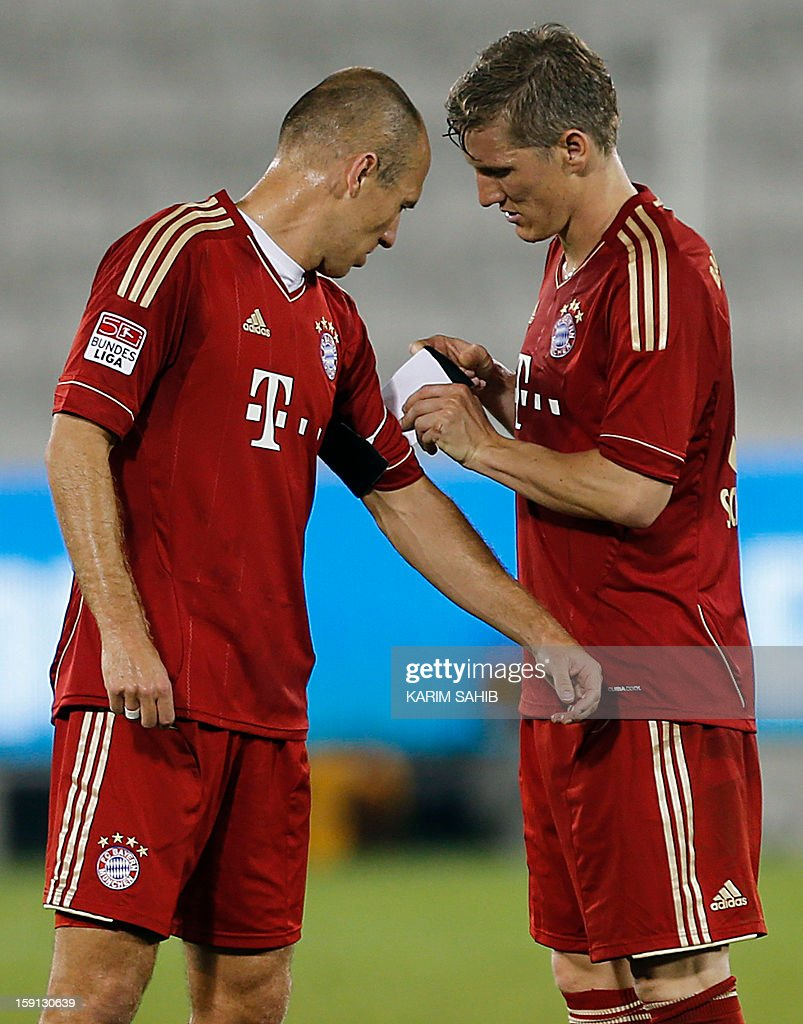 Bayern Munich's German midfielder Bastian Schweinsteiger (R) hands over the captain's armband to Arjen Robben following their friendly match against Schalke in Doha, on January 8, 2013. Bayern Munich and Schalke have been in Qatar for separate training camps before the beginning of the new season of the German Bundesliga after the winter break.