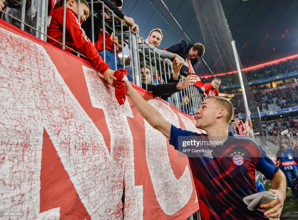 Bayern Munich's German midfielder Joshua Kimmich gives his jersey to a young fan after the Champions League group B match between FC Bayern Munich and Celtic Glasgow in Munich, southern Germany, on October 18, 2017. /