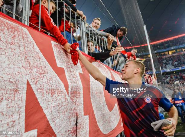 Bayern Munich's German midfielder Joshua Kimmich gives his jersey to a young fan after the Champions League group B match between FC Bayern Munich...