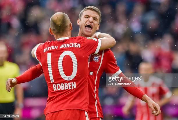 Bayern Munich's German striker Thomas Mueller celebrates scoring the opening goal with Bayern Munich's Dutch midfielder Arjen Robben during the...