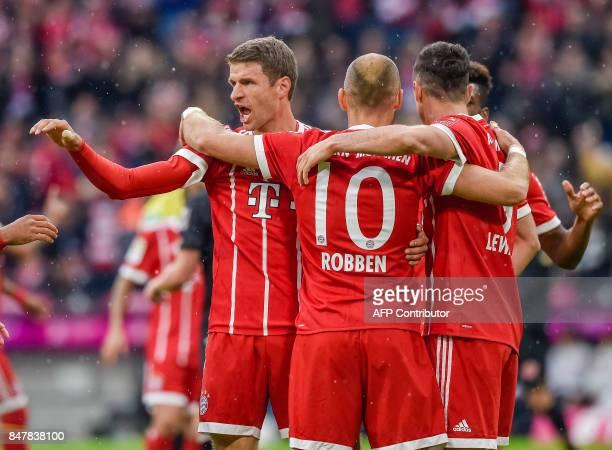 Bayern Munich's German striker Thomas Mueller celebrates scoring the opening goal with Bayern Munich's Dutch midfielder Arjen Robben and Bayern...