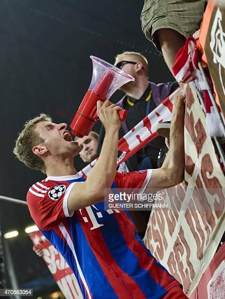 Bayern Munich's German striker Thomas Mueller speaks through a megaphone after the UEFA Champions League secondleg quarterfinal football match Bayern...