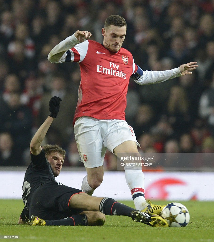 Bayern Munich's German striker Thomas Muller (L) tackles Arsenal's Belgian defender Thomas Vermaelen (R) during the UEFA Champions League round of 16 football match between Arsenal and Bayern Munich at the Emirates Stadium in north London on February 19, 2013. Bayern Munich won 3-1.