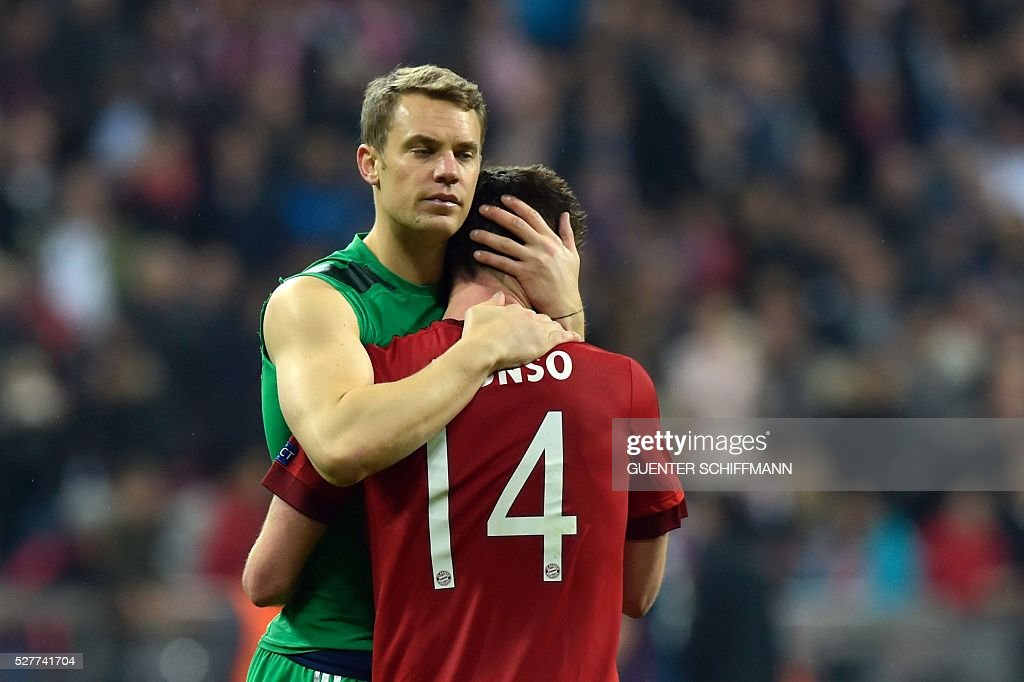 Bayern Munich's goalkeeper Manuel Neuer (L) and Bayern Munich's Spanish midfielder Xabi Alonso comfort eachother after the UEFA Champions League semi-final, second-leg football match between FC Bayern Munich and Atletico Madrid in Munich, southern Germany, on May 3, 2016. / AFP / GUENTER