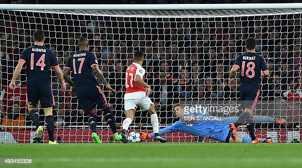 Bayern Munich's goalkeeper Manuel Neuer dives to save a shot from Arsenal's German midfielder Mesut Ozil during the UEFA Champions League football...