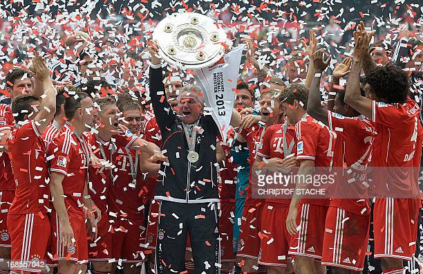 Bayern Munich's head coach Jupp Heynckes holds the German football league champion's trophy while celebrating with his team their champion title...