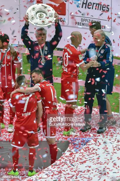 Bayern Munich's Italian head coach Carlo Ancelotti lifts the trophy during the celebrations after the German first division Bundesliga football match...