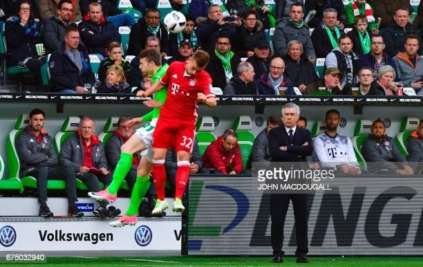 Bayern Munich's Italian head coach Carlo Ancelotti looks on as Bayern Munich's midfielder Joshua Kimmich vies with Wolfsburg's defender Jannes Horn...